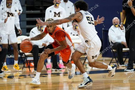 Illinois guard Adam Miller (44) drives on Michigan guard Eli Brooks (55) in the first half of an NCAA college basketball game in Ann Arbor, Mich