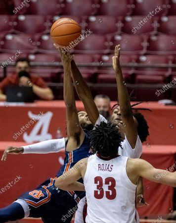 Auburn guard Jamal Johnson, left, shoots as Alabama forward James Rojas (33), forward/guard Herbert Jones (1) and guard John Petty Jr., from front, close in during the first half of an NCAA college basketball game, in Tuscaloosa, Ala
