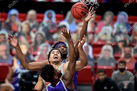 TCU's Owen Aschieris, back, reaches for a rebound over Mikes Miles, front, and Texas Tech's Marcus Santos-Silva, middle, during the first half of an NCAA college basketball game in Lubbock, Texas