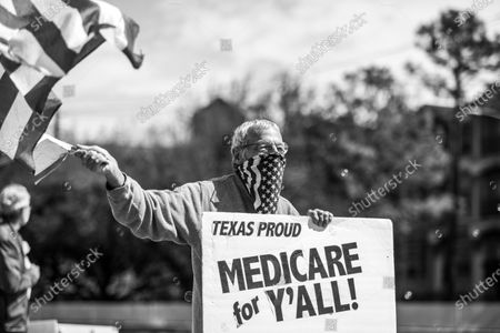 """Protestor Ira Dember waves the American flag and holds a sign reading """"Texas Proud, Medicare for Ya'll"""" in a protest outside of Texas Senator John Cornyn's office on Tuesday, March 2, 2021."""
