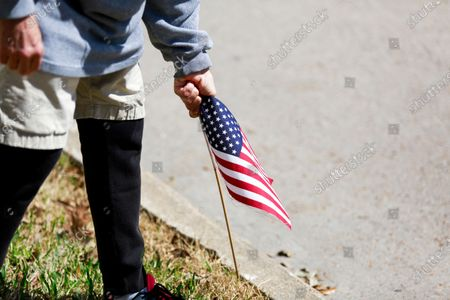 Stock Image of A demonstrator collects miniature american flags and cleans up after a protest outside of Texas senator John Cornyn's office in Houston, Texas on Tuesday, March 2, 2021.
