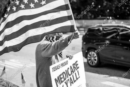 """Stock Photo of Protestor Ira Dember waves the American flag and holds a sign reading """"Texas Proud, Medicare for Ya'll"""" in a protest outside of Texas Senator John Cornyn's office on Tuesday, March 2, 2021."""