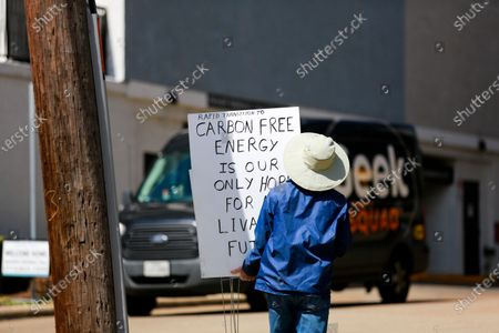 Stock Picture of A demonstrator collects signs after a protest outside of Texas senator John Cornyn's office in Houston, Texas on Tuesday, March 2, 2021.