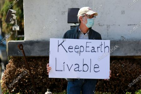 A protestor stands outside of Texas senator John Cornyn's office in Houston, Texas on Tuesday, March 2, 2021.