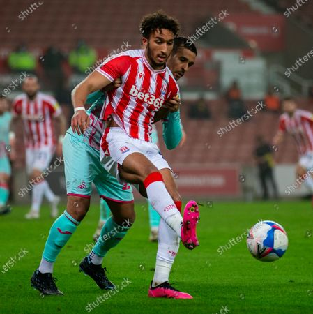 Stock Image of Jacob Brown of Stoke City under pressure from Kyle Naughton of Swansea City; Bet365 Stadium, Stoke, Staffordshire, England; English Football League Championship Football, Stoke City versus Swansea City.