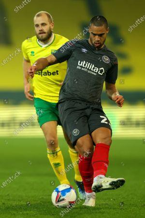 Winston Reid of Brentford plays the ball under pressure from Teemu Pukki of Norwich City; Carrow Road, Norwich, Norfolk, England, English Football League Championship Football, Norwich versus Brentford.