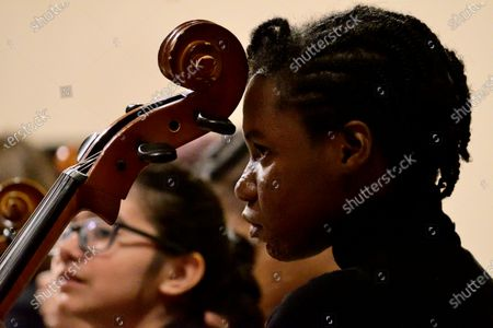 Student Divine Epps rest her head on her cello as Hannibal Lokumbe honors Dr. Kim Phc during a concert that includes Lokumbes composition Children of the Fire, at the Philadelphia Episcopal Cathedral in West Philadelphia, on December 7, 2019. Dr. Phc is the subject of the iconic 1972 Napalm Girl Pulitzer Prize-wining photograph by now-retired Associated Press photographer Nick Ut.