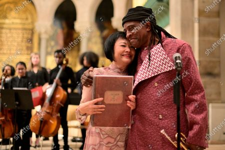 Dr. Kim Phc and Hannibal Lokumbe share a hug after the composer performed his 1973 composition Children of the Fire for the first time in the presence of Dr. Phc, in Philadelphia, PA, on December 7, 2019. Dr. Phc is the subject of the iconic 1972 Napalm Girl Pulitzer Prize-wining photograph by now-retired Associated Press photographer Nick Ut.