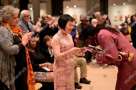 Stock Image of Dr. Kim Phc is honored by Hannibal Lokumbe after the composer performed his 1973 composition Children of the Fire for the first time in the presence of the Girl in the Picture, in Philadelphia, PA, on December 7, 2019. Dr. Phc is the subject of the iconic 1972 Napalm Girl Pulitzer Prize-wining photograph by now-retired Associated Press photographer Nick Ut.