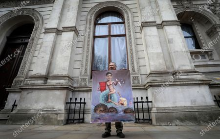 Artist Kaya Mar holds up his painting depicting Chancellor of the Exchequer Rishi Sunak near Downing Street in London, . Britain's Chancellor Rishi Sunak is expected to announce billions of pounds in tax cuts and spending increases to help workers and businesses hit by the coronavirus pandemic when he delivers his budget to Parliament on Wednesday