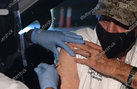 A nurse administers the Moderna COVID-19 vaccine to Robert Fox on the first day that Orange County residents 65 and older are able to be vaccinated at a drive through site at the Orange County Convention Center on December 29, 2020 in Orlando, Florida. Gov. Ron DeSantis has made it a priority to make the coronavirus vaccine available to Floridas elderly population.