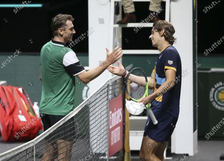 John Millman of Australia checks hands with winner Alex De Minaur of Australia