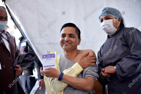Formal Minister of Culture, Tourism and Civil Aviation Yogesh Bhattarai shows vaccination card after getting his first dose of covid-19 vaccine developed by Oxford- AstraZeneca Plc in Civil Hospital, Kathmandu, Nepal on Wednesday, March 3, 2021. Federal lawmakers, parliament secretariat staffers, ministers and senior leaders took their first dose of the vaccine against Covid-19 to attend House session called on March 7, 2021.