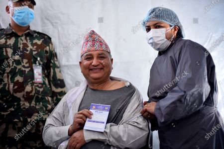 Deputy Prime Minister Ishwar Pokhrel shows vaccination card after getting his first dose of covid-19 vaccine developed by Oxford- AstraZeneca Plc in Civil Hospital, Kathmandu, Nepal on Wednesday, March 3, 2021. Federal lawmakers, parliament secretariat staffers, ministers and senior leaders took their first dose of the vaccine against Covid-19 to attend House session called on March 7, 2021.