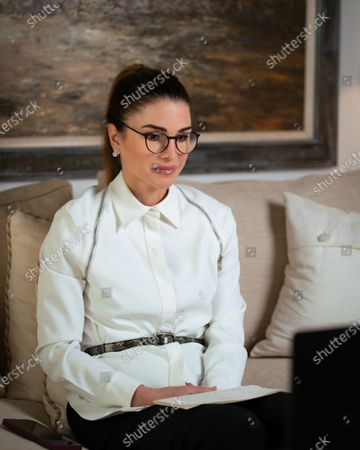 Queen Rania wearing spectacles participates via video conference in the Royal Health Awareness Society's Annual Board of Trustees meeting