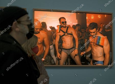 Visitors pass in front of an artwork by British photographer Martin Parr on display during the exhibition 'Parrathon' at the Centre of Carme in Valencia, Spain, 03 March 2021. The exhibition features photographs from the Magnum Photos agency with which Parr works since 1994.