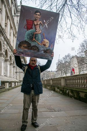 Political satirist Kaya Mar holds a painting outside Downing Street featuring the Chancellor of the Exchequer Rishi Sunakas as he prepares to deliver his budget to Parliament