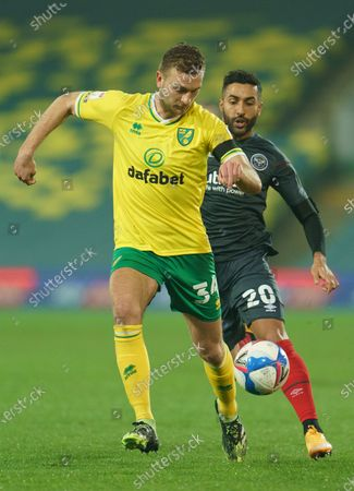 Ben Gibson of Norwich City (34) and Saman Ghoddos of Brentford (20)
