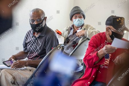 Residents from left, William Bennett, Ming Svay and Louis Williams sit as they wait for 15 minutes after their Covid-19 vaccinations at an affordable housing community on Thursday, Feb. 25, 2021 in Tracy, CA. (Brian van der Brug / Los Angeles Times)