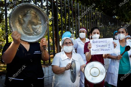 "Stock Image of Respiratory Hospital INERAM health workers bang pots and hold up the Spanish message ""We want supplies! Be strong INERAM!,"" to demand more materials for the ICU, outside their hospital in Asuncion, Paraguay, the day after INERAM Director Felipe Gonzalez resigned. Without vaccines or basic drugs to combat COVID-19, Paraguay's main public hospitals became unable to receive patients in intensive care units on Wednesday"
