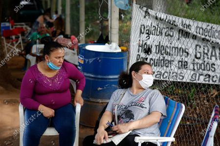 Esther Dominguez, left, and Liz Cristaldo sit outside the ICU of the Respiratory Hospital INERAM where their relatives are being treated for COVID-19 in Asuncion, Paraguay, the day after INERAM Director Felipe Gonzalez resigned. Without vaccines or basic drugs to combat COVID-19, Paraguay's main public hospitals became unable to receive patients in intensive care units on Wednesday
