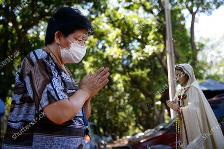 Woman prays before a statue of the Virgin Mary outside the ICU of the Respiratory Hospital INERAM where she has a family member being treated for COVID-19 in Asuncion, Paraguay, . Without vaccines or basic drugs to combat COVID-19, Paraguay's main public hospitals became unable to receive patients in intensive care units on Wednesday, triggering INERAM Director Felipe Gonzalez to resign in protest