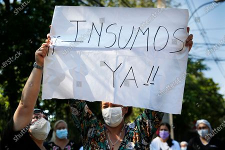 "Stock Photo of Patient's relative holds up the Spanish message ""Supplies now!"" outside the Respiratory Hospital INERAM during a protest demanding more materials for the ICU outside the hospital in Asuncion, Paraguay, . Without vaccines or basic drugs to combat COVID-19, Paraguay's main public hospitals became unable to receive patients in intensive care units on Wednesday, triggering the resignation of INERAM Director Felipe Gonzalez in protest"
