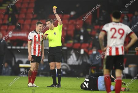 Referee Robert Jones shows a yellow card to Sheffield United's Phil Jagielka as he fouled Aston Villa's Anwar El Ghazi, bottom, during the English Premier League soccer match between Sheffield United and Aston Villa at Bramall Lane stadium in Sheffield, England