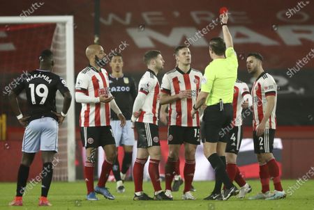 Referee Robert Jones shows a red card to Sheffield United's Phil Jagielka during the English Premier League soccer match between Sheffield United and Aston Villa at Bramall Lane stadium in Sheffield, England