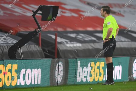 Referee Robert Jones watching the VAR monitor, during the English Premier League soccer match between Sheffield United and Aston Villa at Bramall Lane stadium in Sheffield, England
