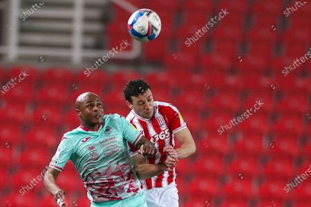 Swansea City forward Andre Ayew (10) goes for a header with Stoke City defender James Chester (12) during the EFL Sky Bet Championship match between Stoke City and Swansea City at the Bet365 Stadium, Stoke-on-Trent
