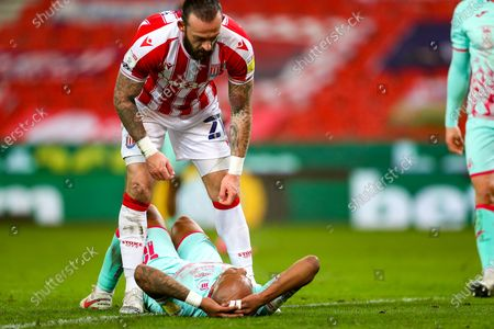 Stoke City forward Steven Fletcher (21) picks Swansea City forward Andre Ayew (10) up during the EFL Sky Bet Championship match between Stoke City and Swansea City at the Bet365 Stadium, Stoke-on-Trent