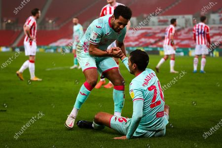 Swansea City defender Kyle Naughton (26) is picked up by Swansea City midfielder Korey Smith (7) after winning a penalty during the EFL Sky Bet Championship match between Stoke City and Swansea City at the Bet365 Stadium, Stoke-on-Trent