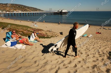 Editorial image of People visit the Malibu Pier built in 1905 which features shops, fishing, people watching and restaurants open for outside dinning as Malibu and Playa del Rey have avoided the COVID winter surge, Malibu, California, United States - 22 Feb 2021