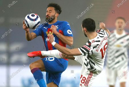 Crystal Palace's Andros Townsend, left, and Manchester United's Bruno Fernandes challenge for the ball during the English Premier League soccer match between Crystal Palace and Manchester United at Selhurst Park stadium in London, England