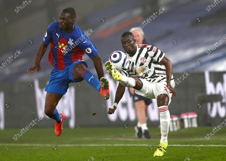 Crystal Palace's Christian Benteke, left, and Manchester United's Eric Bailly challenge for the ball during the English Premier League soccer match between Crystal Palace and Manchester United at Selhurst Park stadium in London, England