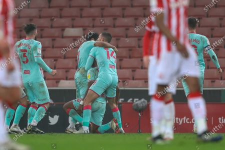 Swansea City players celebrate a last minute successful penalty kick by Andre Ayew of Swansea City