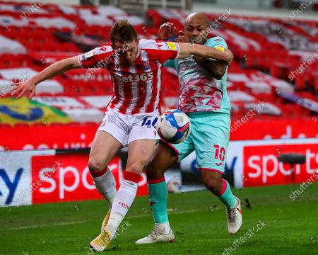 Andre Ayew of Swansea City and Rhys Norrington-Davies of Stoke City tussle for the ball