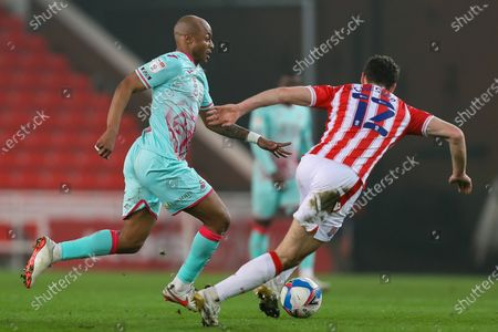 Andre Ayew of Swansea City bursts past James Chester of Stoke City
