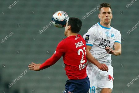 Lille's Benjamin Andre, left, jumps for a header with Marseille's Arkadiusz Milik during the French League One soccer match between Lille and Marseille at the Stade Pierre Mauroy stadium in Villeneuve-d'Ascq, France