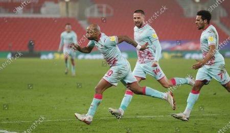 Stock Photo of Andre Ayew of Swansea celebrates scoring a penalty with Korey Smith and Conor Hourihane