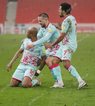 Andre Ayew of Swansea celebrates scoring a penalty with Korey Smith and Conor Hourihane