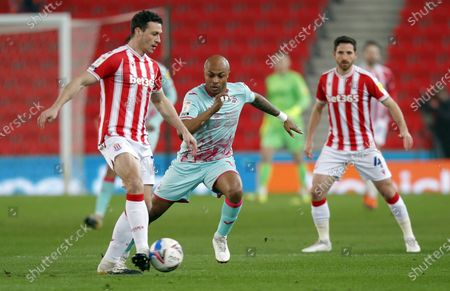 Andre Ayew of Swansea tries to take the ball from James Chester of Stoke City