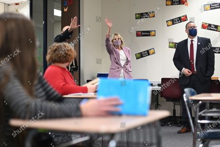 First lady Jill Biden waves as she and Education Secretary Miguel Cardona tour Fort LeBoeuf Middle School in Waterford, Pa