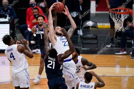 Seton Hall forward Sandro Mamukelashvili (23) grabs the ball in front of Connecticut forward Adama Sanogo (21) as Seton Hall forward Tyrese Samuel (4) and Connecticut guard R.J. Cole (1) watch during the second half of an NCAA college basketball game, in Newark, N.J