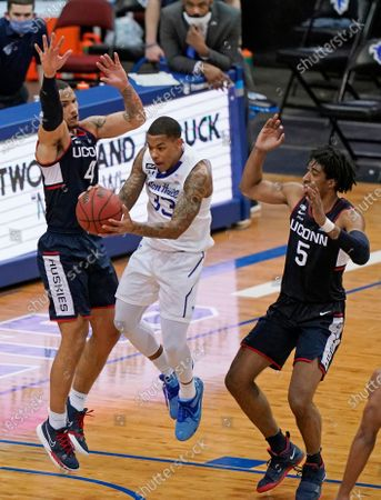 Connecticut guard Tyrese Martin (4) and forward Isaiah Whaley (5) defend against Seton Hall guard Shavar Reynolds (33) during the second half of an NCAA college basketball game, in Newark, N.J