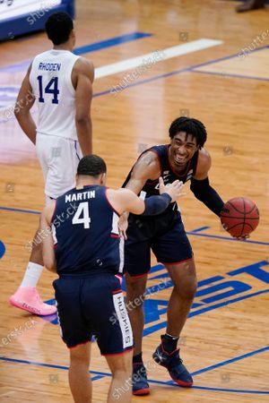 Connecticut forward Isaiah Whaley (5) congratulates guard Tyrese Martin (4) after an NCAA college basketball game against Seton Hall, in Newark, N.J