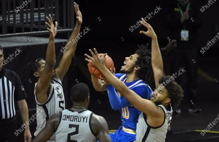 Guard Tyger Campbell (10) is fouled by Oregon guard LJ Figueroa (12) as Oregon forward Eric Williams Jr. (50) and Oregon forward Eugene Omoruyi (2) come in on the play during the second half of an NCAA college basketball game, in Eugene, Ore