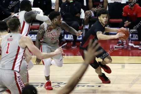 San Diego State's Trey Pulliam (4) looks for an open pass against UNLV's David Jenkins Jr. (5) during the second half of an NCAA college basketball game, in Las Vegas
