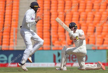 India's Shubman Gill, left, reacts as England's Dan Lawrence, right, plays a shot during the first day of fourth cricket test match between India and England at Narendra Modi Stadium in Ahmedabad, India